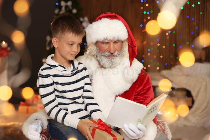 Little child with Santa Claus reading Christmas story at. Home royalty free stock photo