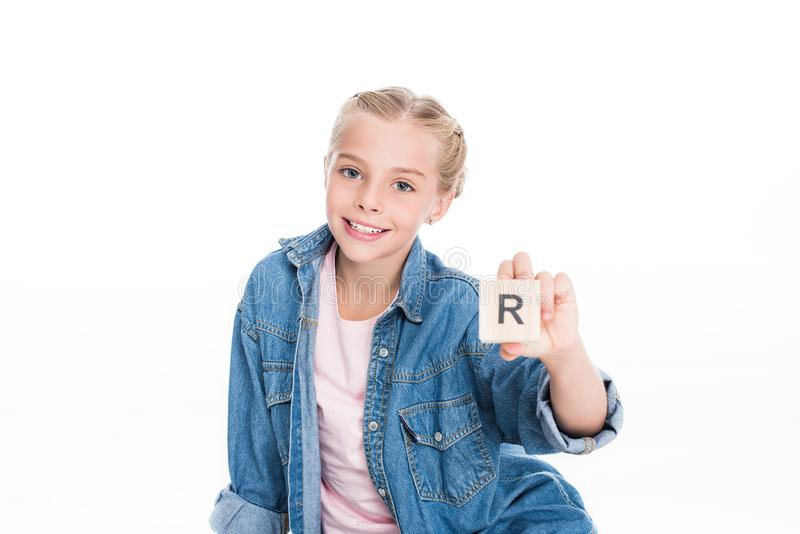 Little child showing a letter cube with R engraved on it, royalty free stock photography