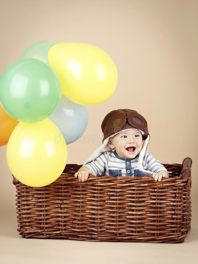 Little child sitting in the basket with baloons royalty free stock image
