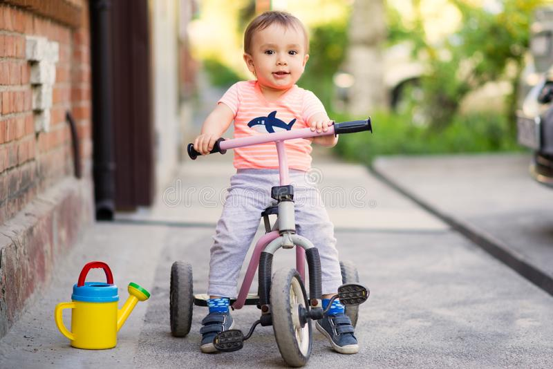 Little child sitting on a pink tricycle on an asphalt tarmac pavement. Portrait of a little child on a three wheel bike tricycle on a tarmac pavement in a warm stock images