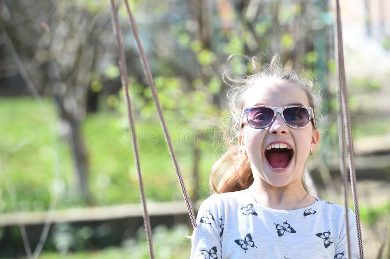 Little child smile on swing in summer yard. Fashion girl in sunglasses enjoy swinging on sunny day. Beauty kid smiling on playgrou stock photos