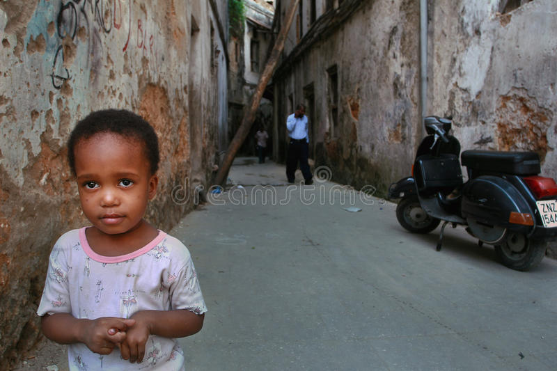 Little child standing in a courtyard an old dilapidated house. royalty free stock photography