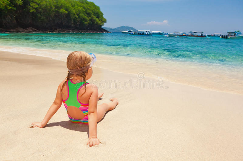 Little child on summer family holidays on tropical beach. Beautiful little snorkeler relax on sunny white sand ocean beach. Happy baby have fun, look at surf in royalty free stock photography