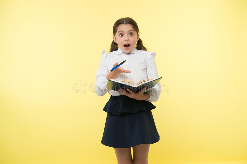 Little child with surprised look. Schoolgirl with long hair hold book with pen. Fashion genius. Back to school. Home royalty free stock photo