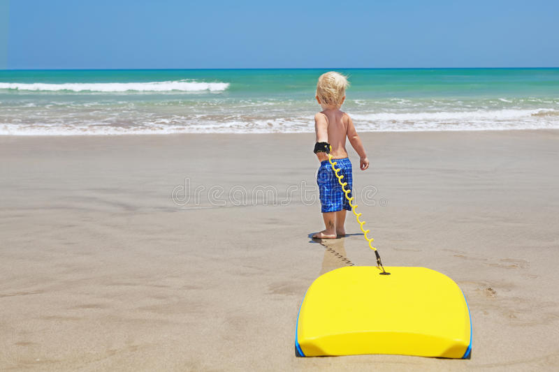 Little child swimming with bodyboard on the sea sand beach royalty free stock images
