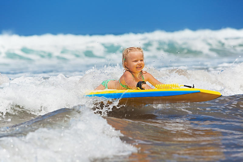 Little child swimming with bodyboard on the sea waves. Little baby girl - young surfer with bodyboard has a fun on small sea waves. Active family lifestyle royalty free stock photo