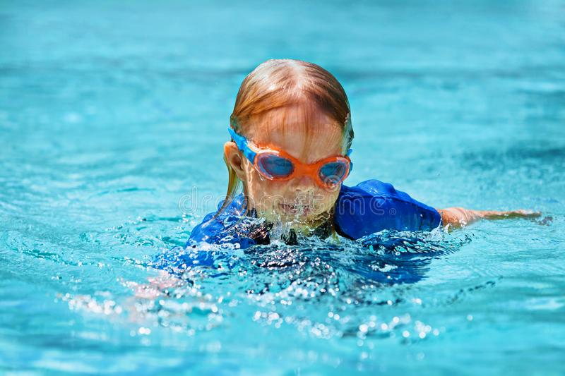 Little child swimming lesson in outdoor pool. Happy child in wetsuit and goggles learn to swim, have fun in outdoor pool. Healthy family lifestyle, little kids stock photo