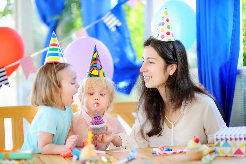 Little child and their mother celebrate birthday party with colorful decoration and cakes stock images