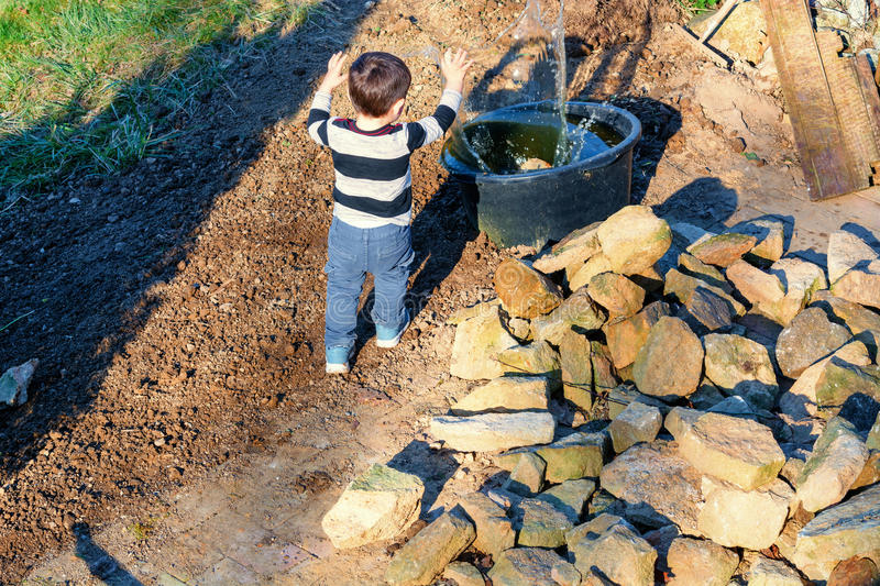 Little child throwing pebbles into the water stock photos