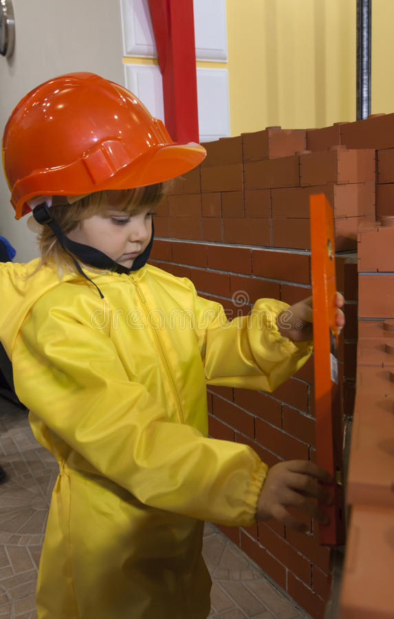 Little child with tool near the brick wall. Little boy hard hat and yellow overalls holding a construction bubble level near the brick wall stock photo