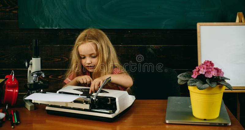 Little child type on typewriter at desk. Girl learn typing on retro typewriter in school stock photography