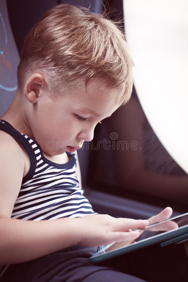 Little child using touch pad while traveling by stock images