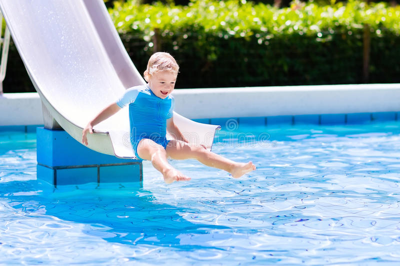 Little child on water slide in swimming pool. Happy laughing little boy playing on water slide in outdoor swimming pool on a hot summer day. Kids learn to swim royalty free stock images