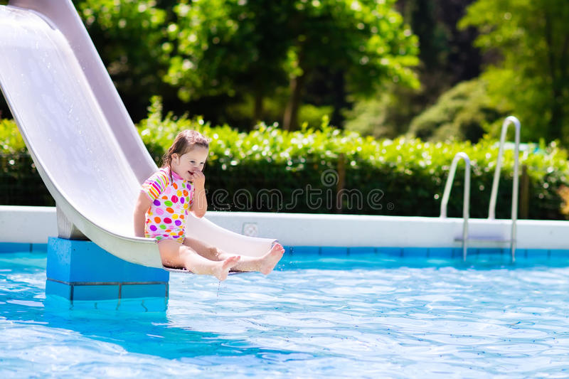 Little child on water slide in swimming pool. Happy laughing little girl playing on water slide in outdoor swimming pool on hot summer day. Kids learn to swim royalty free stock images