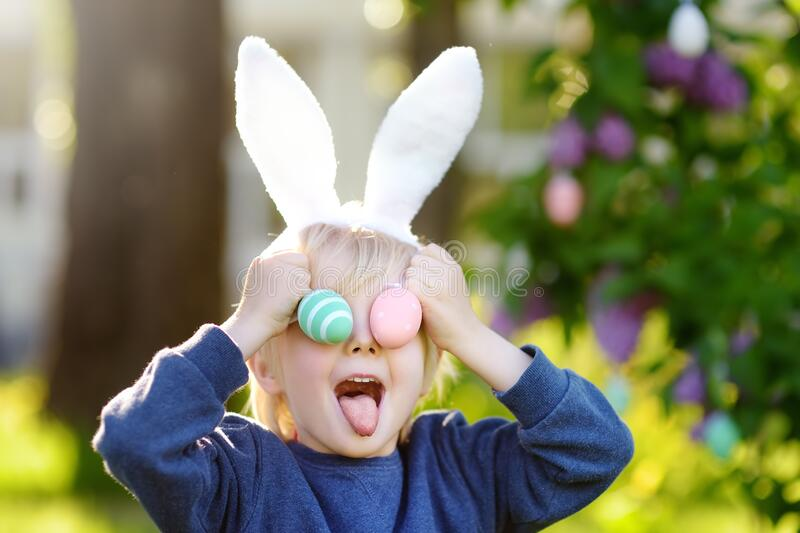 Little child wearing bunny ears playing with easter eggs in spring park on Easter day stock photography