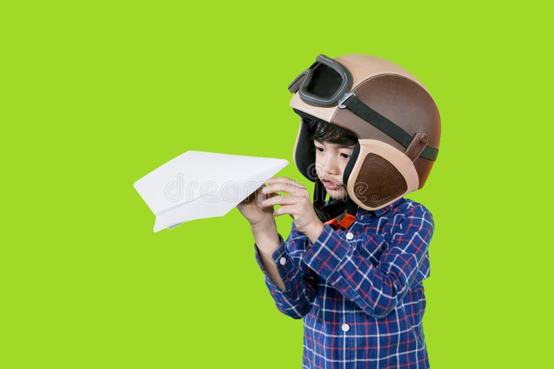 Little child wears helmet during play a paper plane. Picture of little child wearing flight helmet while playing a paper plane in the studio with green screen royalty free stock photo