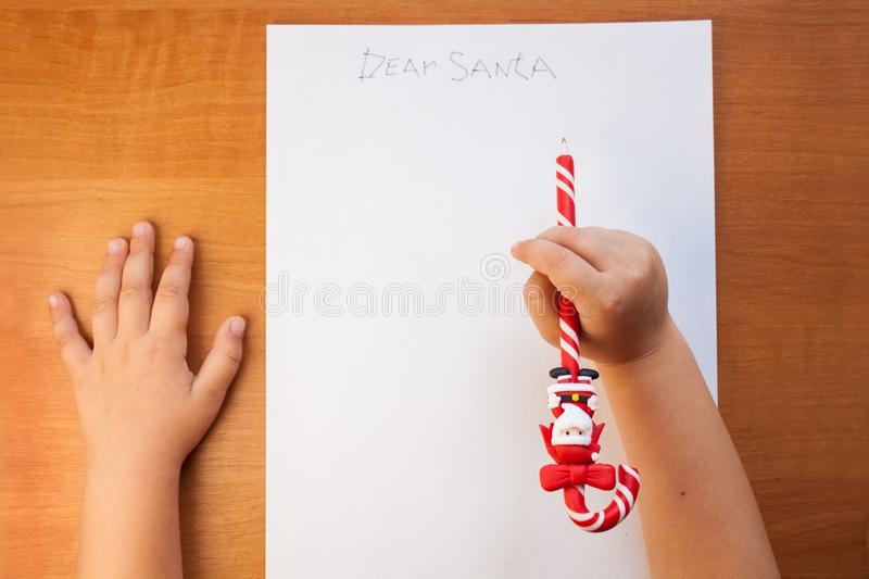 Little child writing letter to Santa at Christmas at home on a wooden table in the living room. Copy space, flatlay. Little child writing letter to Santa at royalty free stock photo
