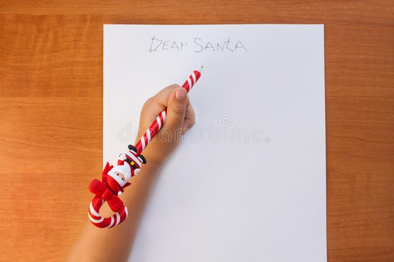 Little child writing letter to Santa at Christmas at home on a wooden table in the living room. Copy space, flatlay. Little child writing letter to Santa at stock image