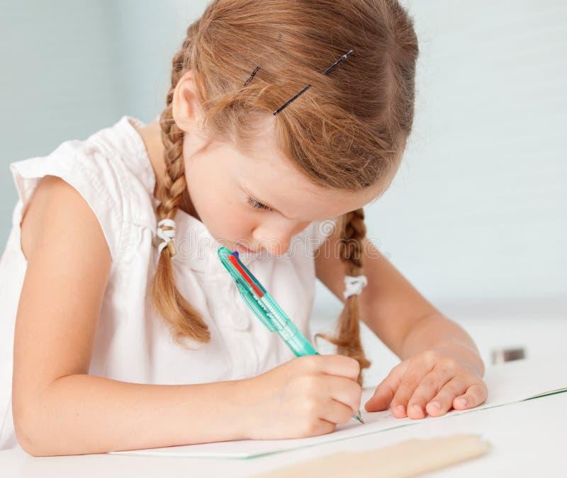 Little child writing. Preschool girl doing homework royalty free stock photos