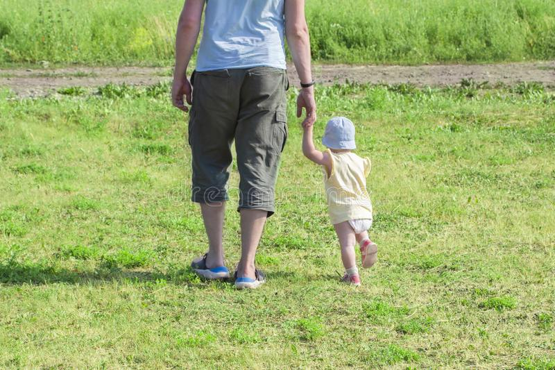 Little child 1 year old baby girl goes holding dad`s hand. The father walks with the child through the green grass. Baby learns t royalty free stock image