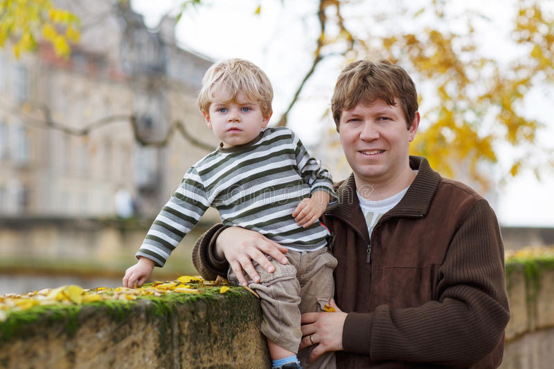 Download Little Child And Young Father In Autumn City Stock Photo - Image: 41724174