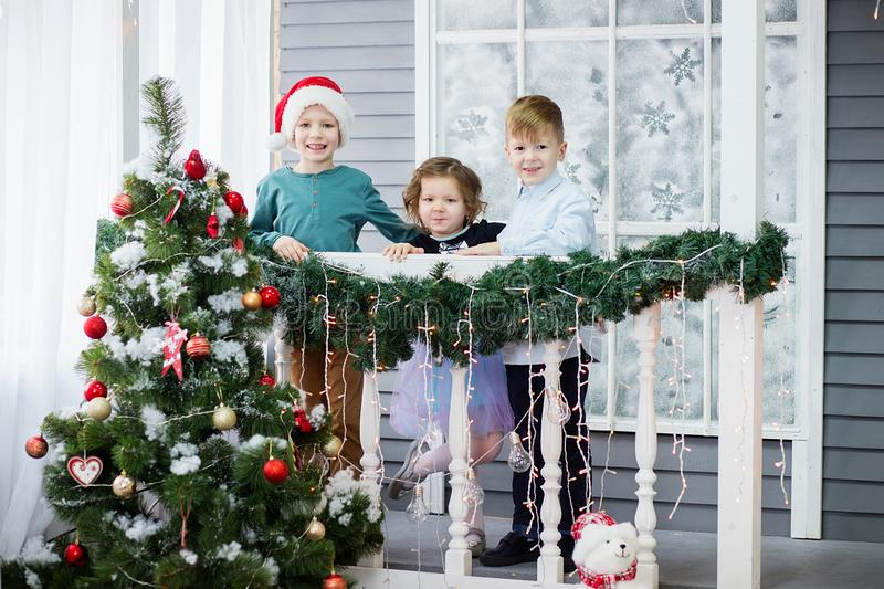 Little children In anticipation of new year and Christmas. Three little Kids are having fun and playing near Christmas tree royalty free stock images