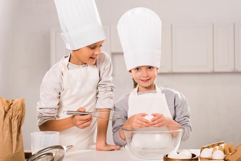 Little children in aprons and chef hats preparing at table. In kitchen royalty free stock images