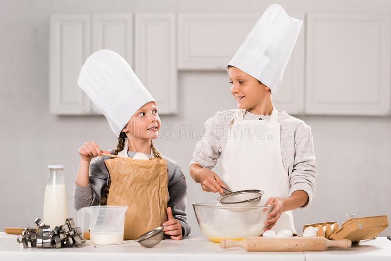 Little children in aprons and chef hats preparing at table. In kitchen stock images