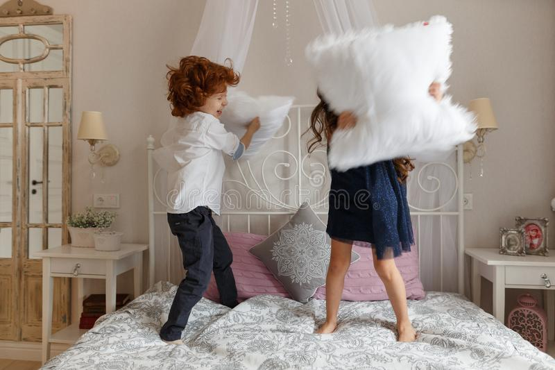 Little children, boy and girl fighting with pillows stock photography