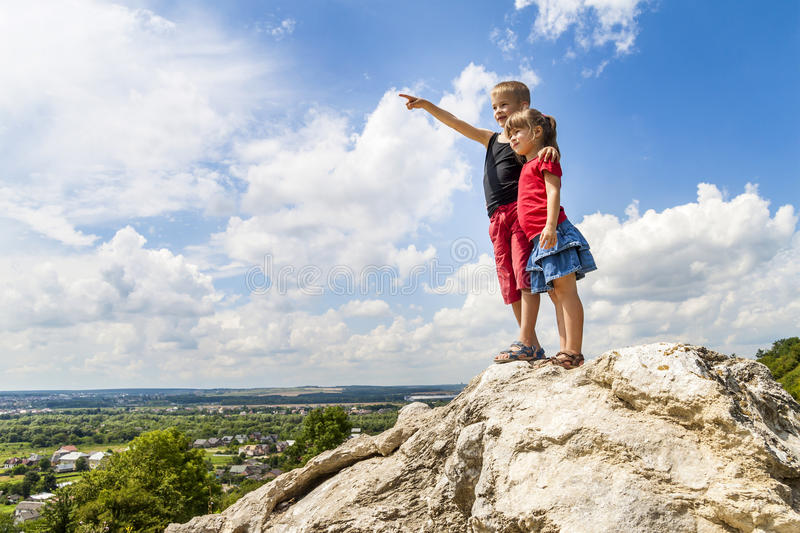 Little children boy and girl standing on mountain rock and looking ahead. Boy showing with his hand stock photos