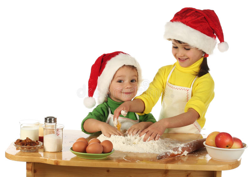 Little children cooking the Christmas cake stock images