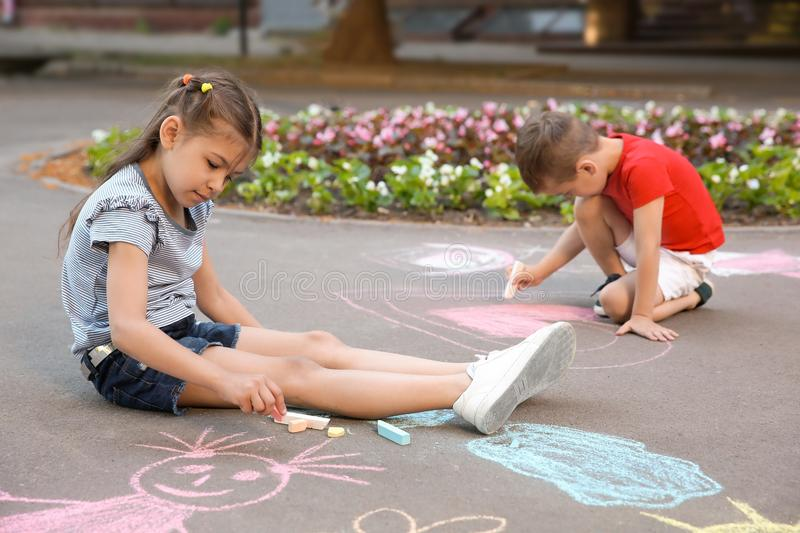Little children drawing with colorful chalk royalty free stock photo