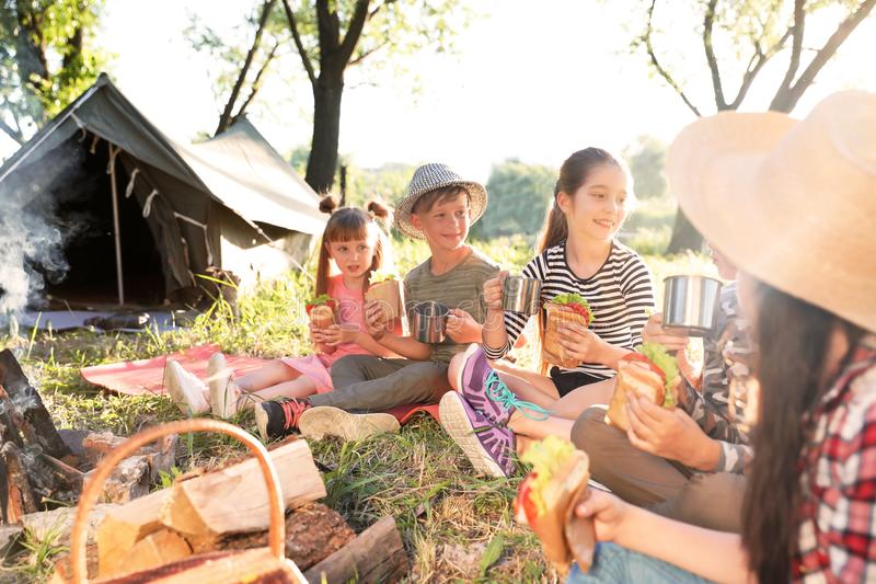 Little children eating sandwiches near bonfire royalty free stock images
