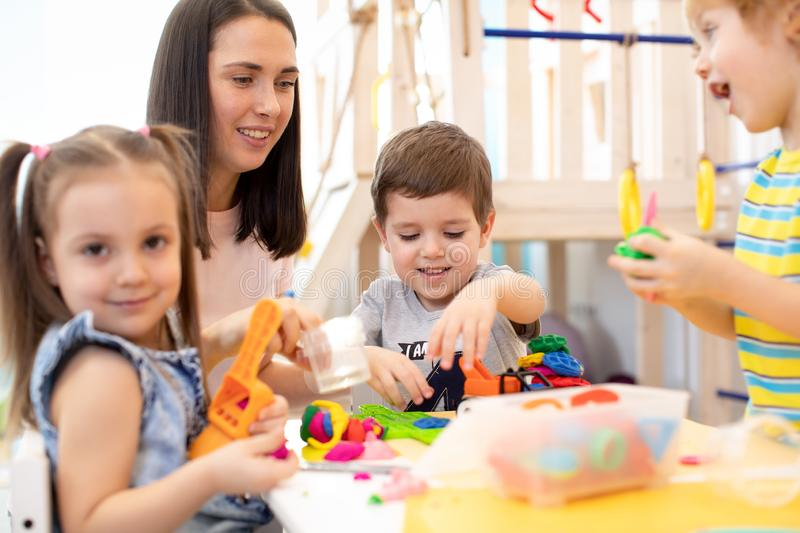 Little children engaged in playdough modeling at daycare stock photos