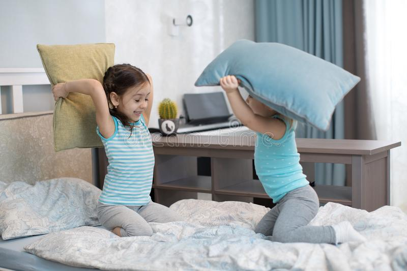 Little girls fighting using pillows in bedroom royalty free stock photo
