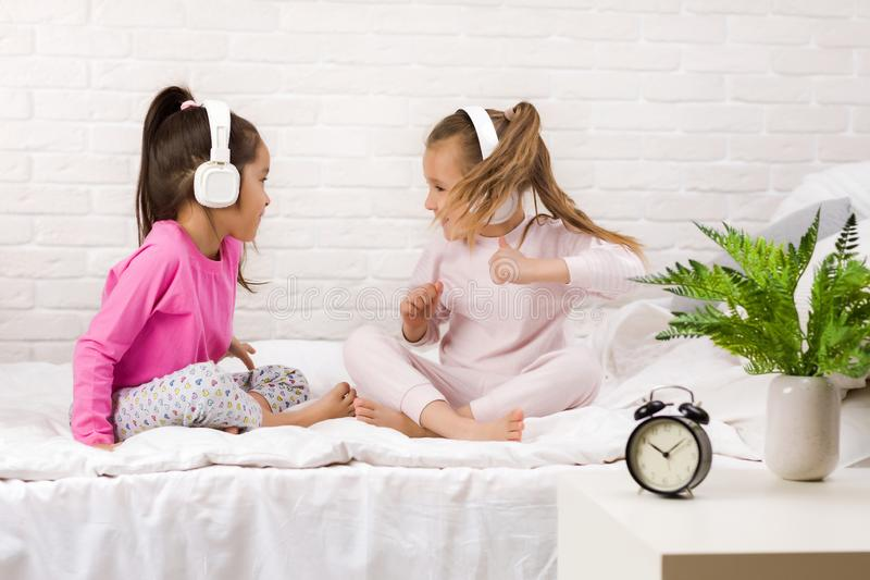 Little children girls listening to the music with the headphones and dancing on bed. Pajama party and friendship stock photo