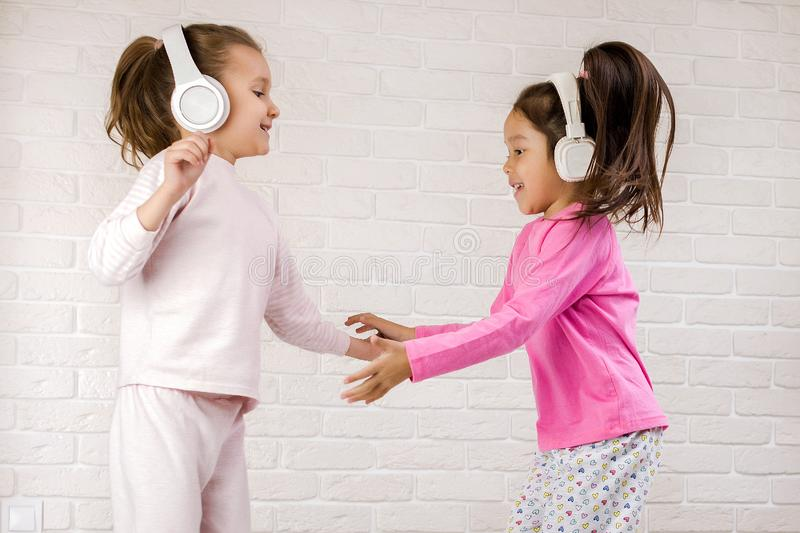 Little children girls listening to the music with the headphones and dancing on bed. Pajama party and friendship royalty free stock photography