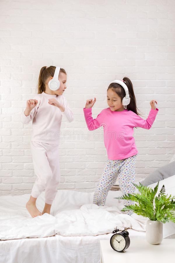 Little children girls listening to the music with the headphones and dancing on bed. Pajama party and friendship stock images
