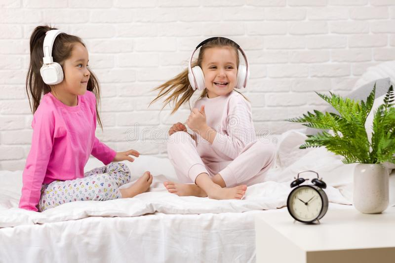Little children girls listening to the music with the headphones and dancing on bed. Pajama party and friendship stock photography
