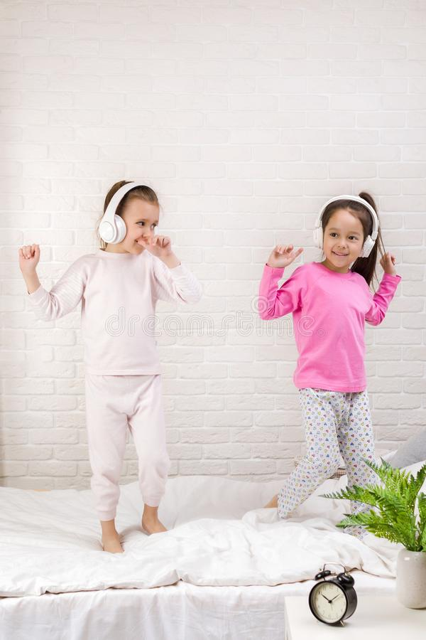 Little children girls listening to the music with the headphones and dancing on bed. Pajama party and friendship stock photos