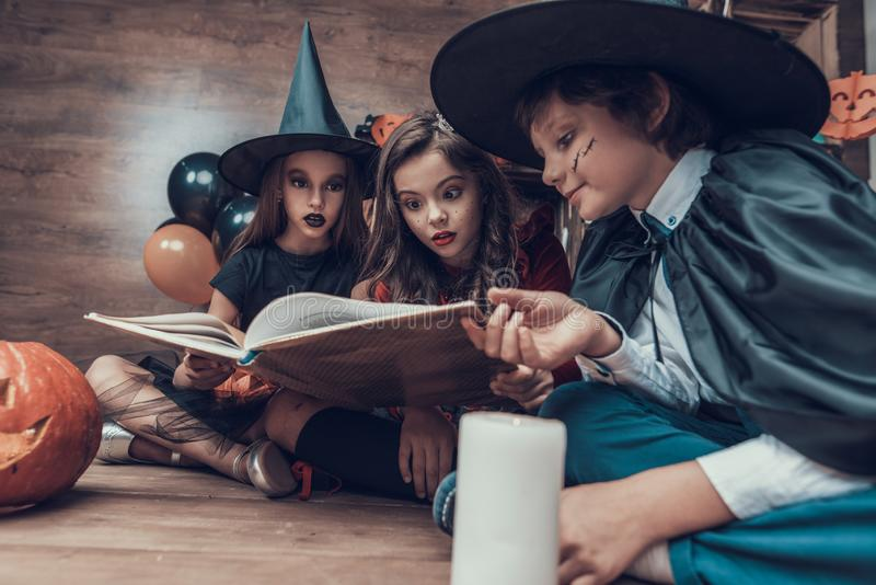 Little Children in Halloween Costumes Reading Book royalty free stock images