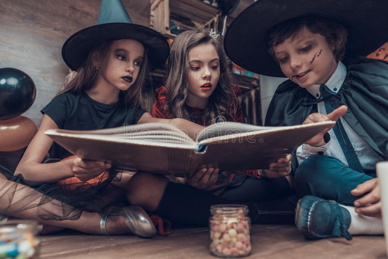Little Children in Halloween Costumes Reading Book stock photography