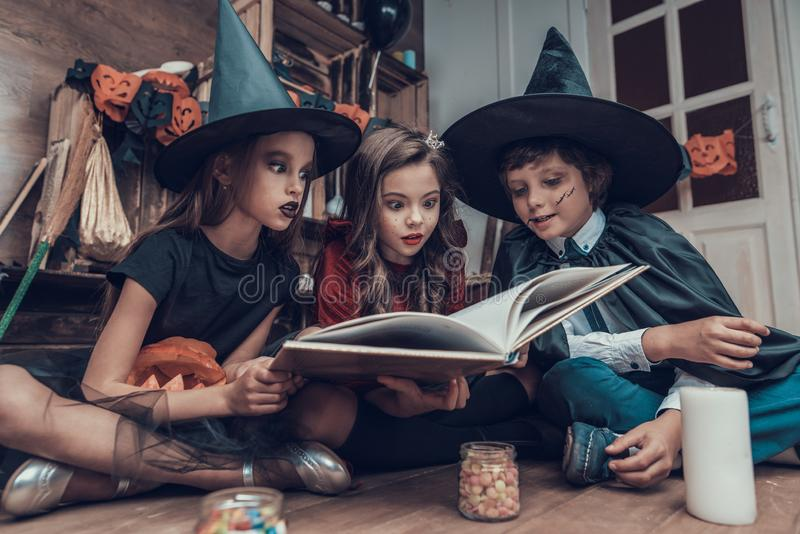 Little Children in Halloween Costumes Reading Book royalty free stock photography