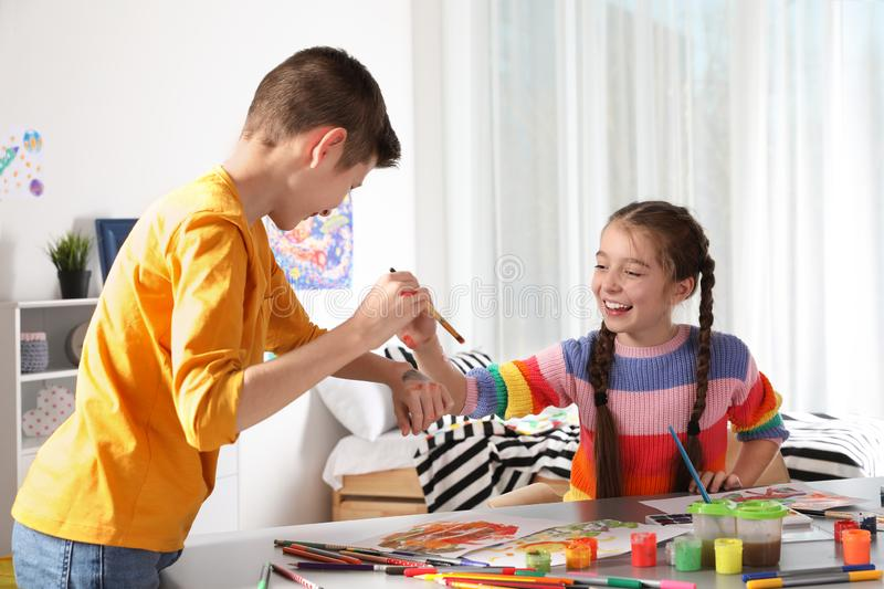 Little children having fun with paints at table stock photos