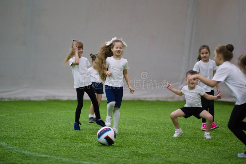Little children kicking the ball on the field and laughing playing football stock photography