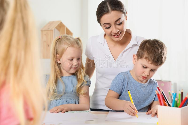 Little children with kindergarten teacher drawing at table. Learning and playing stock photos