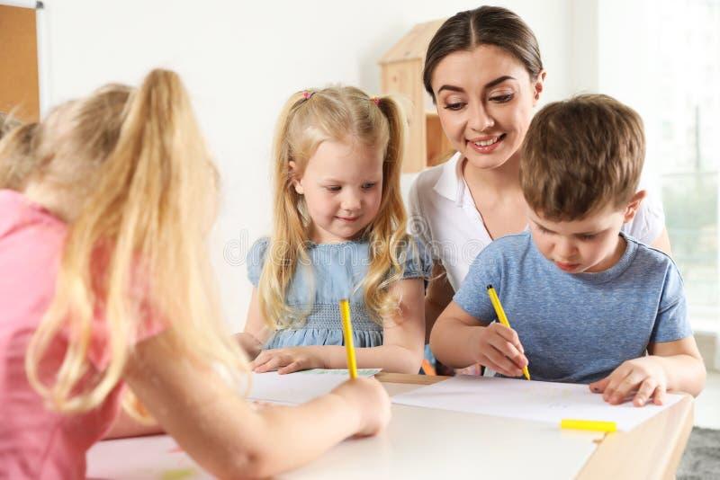 Little children with kindergarten teacher drawing at table indoors stock image