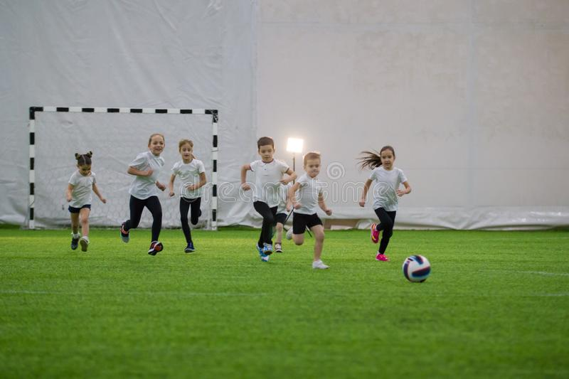 Little children plaiying football on the field running after the ball and smiling royalty free stock photos