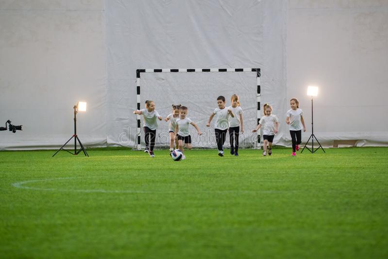 Little children plaiying football running across the field stock images