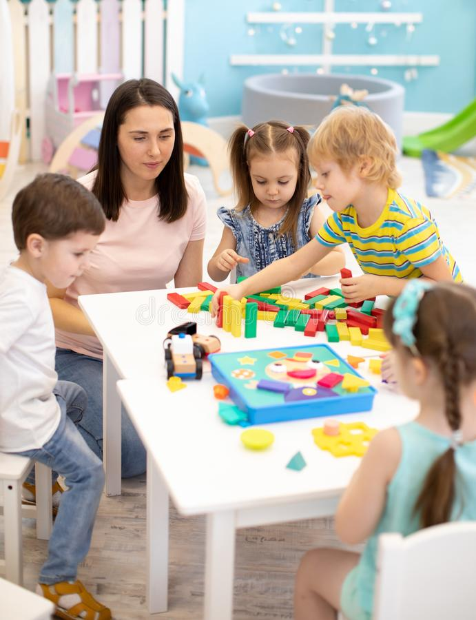 Little children play with different toys with teacher in daycare. Kids building color blocks. Educational toys for stock photos